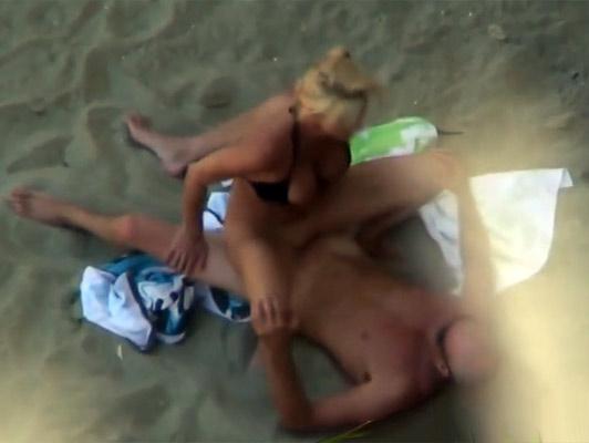 Imagen Voyeur en la playa con la camara de video graba una pareja follando en la arena
