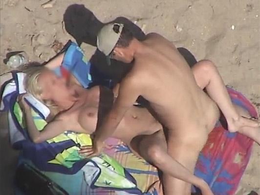 Imagen Mirón grabando a una pareja, follando en la playa ella es una rubia con grandes tetas
